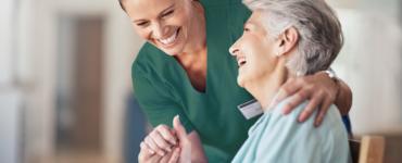 happy nurse in green scrubs helping elderly grandmother in wheelchair ta