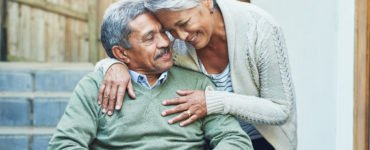 Cheerful elderly man seated in a wheelchair while being held by his loving wife outside at home during the day