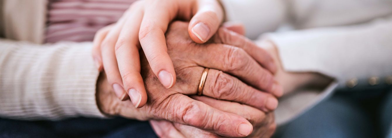 teenage girl with grandmother at home, holding hands